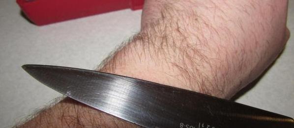Нож срезает волосы на руке